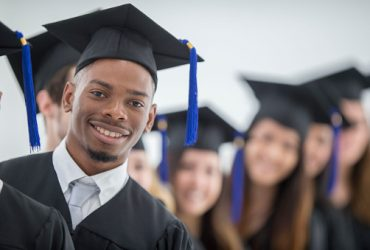 A multi-ethnic group of college graduates are standing in a row and are smiling and looking at the camera. They are all wearing their graduation cap and gowns and are ready to march for graduation.